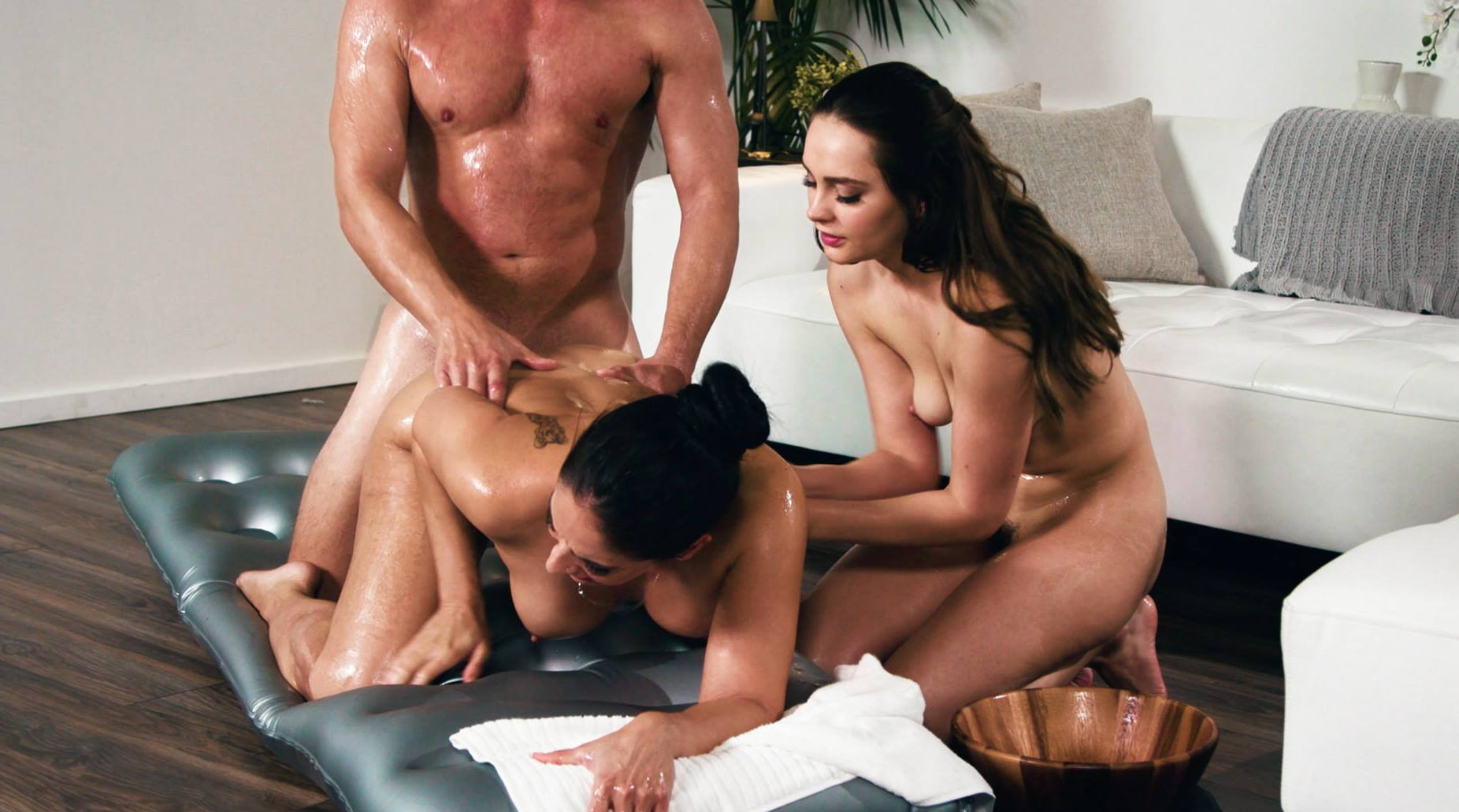 Lubed masseuses spreading wide and riding cock in threesome